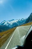 Driving to the mountains. A car, a road, and the mountains in New Zealand, where you drive on the left (and the driver is on the right). Mountains with glaciers Stock Photos