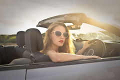 Driving to the Sun. Woman driving Convertible car under the rays of the Sun royalty free stock images