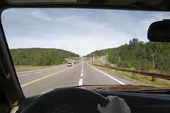 Driving to Work. View of the road from behind a steering wheel, with hands on the wheel Royalty Free Stock Photography