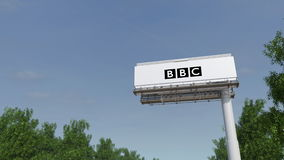 Driving towards advertising billboard with British Broadcasting Corporation BBC logo. Editorial 3D rendering 4K clip. Driving towards advertising billboard with stock video footage