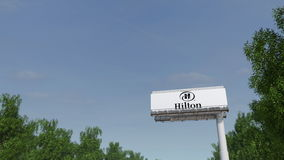 Driving towards advertising billboard with Hilton Hotels Resorts logo. Editorial 3D rendering. Driving towards advertising billboard with Hilton Hotels Resorts Stock Photo