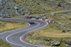 Driving on Transfagarasan mountain winding road, from Carpathian mountains in Romania in classic vintage sports. Stock Photos