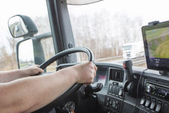 Driving truck. The truck driver while driving. Holding hands on the wheel. White truck is in the opposite direction on the highway.Navigation is mounted on the Stock Photo