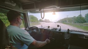 Driving truck. Truck driver delivering freight. Inside the cabin with solar rays in the cabin