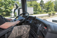 Driving truck. View from the truck cab for the driver who holds the steering wheel. White truck is passing  in the opposite. All potential trademarks are removed Royalty Free Stock Image