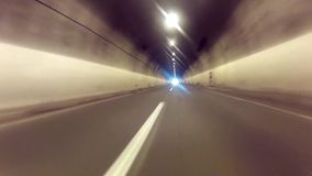 Driving through tunnel. Driving POV freeway time lapse through tunnel heading toward paradise light stock video
