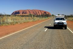 Driving beside Uluru Stock Photo