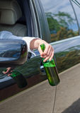 Driving Under the Influence. Female hand with bottle of beer stock photo