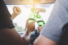 Driving under the influence get into accident, Two asian man drives a car with drunk a bottle of beer alcohol behind the steering. Driving under the influence royalty free stock photos