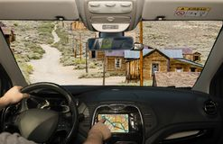 Driving while using navigation system in Bodie, California, USA. Driving a car while using the touch screen of a GPS navigation system in the gold mining ghost royalty free stock image