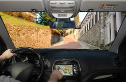 Driving while using navigation system on the slope to the Udine. Driving a car while using the touch screen of a GPS navigation system on the slope to the Udine royalty free stock images