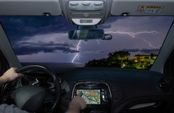 Driving while using navigation system towards lightning over the. Driving a car while using the touch screen of a GPS navigation system towards lightning over stock photo