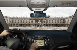 Driving while using navigation system towards Somerset House, Lo. Driving a car while using the touch screen of a GPS navigation system towards Somerset House royalty free stock photos