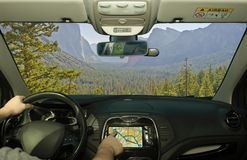 Driving using navigation system towards a valley, Yosemite Park, USA. Driving a car while using the touch screen of a GPS navigation system towards a beautiful royalty free stock photos