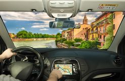 Driving while using navigation system in Verona, Italy. Driving a car while using the touch screen of a GPS navigation system in Verona, Italy royalty free stock photos