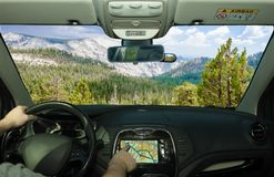 Driving while using navigation system in Yosemite National Park, USA. Driving a car while using the touch screen of a GPS navigation system in Yosemite National royalty free stock photo