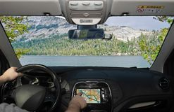 Driving using navigation system in Yosemite National Park, USA. Driving a car while using the touch screen of a GPS navigation system towards a beautiful green royalty free stock photo