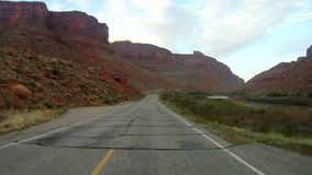 Driving through Utah. Driving on deserted road through red rock buttes of Utah stock video footage