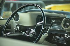 Driving a vintage car. View of dashboard, steering wheel, indicators and timing gauges of a vintage American car with all the details of the interior visible Royalty Free Stock Photo