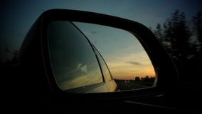 Driving with vivid sunset in rear mirror. Car driving with vivid sunset (sun going down) in read side mirror. Other cars are reflected as well as the trees and stock footage