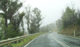 Driving on a wet road in Tasmania. Clouds on road in Beautiful Tasmania country side village in the town of Sorell to Port Arthur, Australia Stock Photo