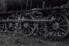 Driving wheels from an old steam locomotive. Old abandoned steam locomotive standing on some old tracks with grass and bushes growing on it Stock Images