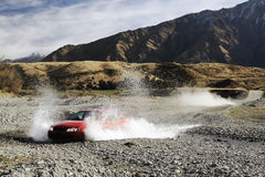 Driving wild. Car at speed through a river crossing stock images