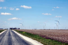 Driving through a Wind Turbine Farm. A country road alongside a wind turbine farm Royalty Free Stock Images