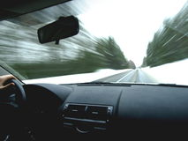 Driving in winter. A car zooming down a road in the winter while driving a car