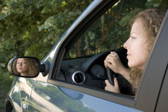 Driving woman reflecting in rear mirror Royalty Free Stock Photos