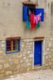 driying在太阳、蓝色窗口和窗帘的洗衣店 免版税库存图片