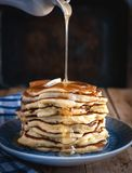 Stack of pancakes with butter and drizzling honey on wooden background royalty free stock image