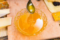 Drizzling honey from a spoon into a bowl Stock Photos