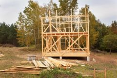 Drizzly autumn day at the construction site. Construction of a wooden house in the forest. Construction of the house. Stock Image