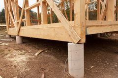 Drizzly autumn day at the construction site. Construction of a wooden house in the forest. Construction of the house. Stock Photos