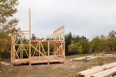 Drizzly autumn day at the construction site. Construction of a wooden house in the forest. Construction of the house. Royalty Free Stock Images
