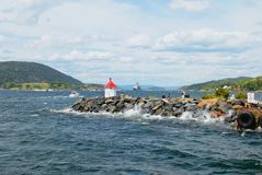People enjoy the view to the fjord from a lighthouse at the entrance to the harbor in Drobak, Norway. stock photos