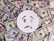 droefheid emoticon op wit en achtergrond met Amerikaanse dollarsbankbiljetten Stock Afbeeldingen
