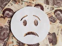 droefheid emoticon op wit en achtergrond met Mexicaanse bankbiljetten Royalty-vrije Stock Fotografie