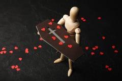 Droefheid en lijkzang Een houten mens houdt een doodskist in zijn handen met rode harten van verdriet stock foto