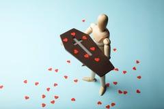 Droefheid en lijkzang Een houten mens houdt een doodskist in zijn handen met rode harten van verdriet stock fotografie