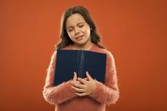 Droevig be?indigend verhaal Het gelezen verhaal van de meisjesgreep boek over oranje achtergrond Het kind geniet van lezend boek  royalty-vrije stock afbeelding