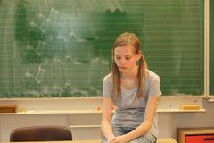 Droevig blonde meisje in school stock afbeeldingen