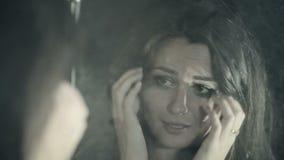 Droevig donkerbruin meisje die haar gedachtengang in de spiegel bekijken stock video