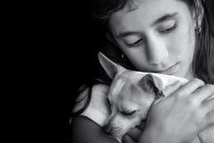 Droevig eenzaam meisje die haar kleine hond koesteren Stock Afbeeldingen