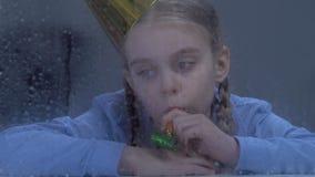 Droevig eenzaam meisje die met partijventilator in venster op regen kijken, die geen vrienden hebben stock footage