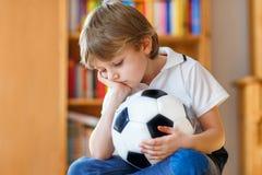 Droevig en niet gelukkig weinig jong geitje met voetbal over verloren voetbal of voetbalspel kind na het letten van op gelijke op royalty-vrije stock foto's