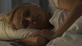 Droevig gepensioneerdewijfje die op smartphone babbelen en aan slaap, slapeloosheid proberen stock videobeelden