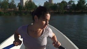 Droevig jong meisje die in een boot roeien stock videobeelden