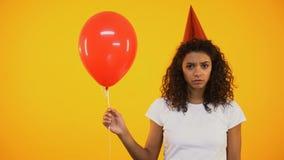 Droevig jong meisje die rode die ballon houden, en eenzaam op verjaardagsviering wordt verstoord stock videobeelden